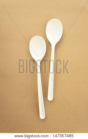 Twin spoons on brown background White spoon The device is one of the cooking container. in eating