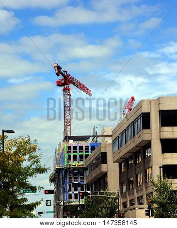 New construction of a building downtown Madison Wisconsin has tall red crane working over building. Blue sky frames tall red boom.