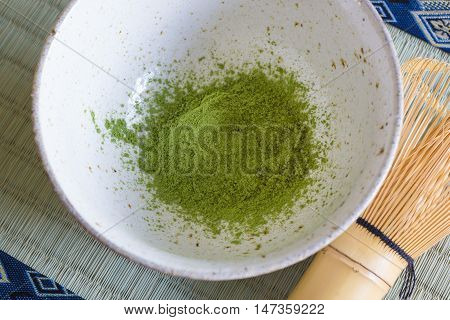 Japanese Matcha green tea powder in a chawan or traditional ceramic bowl with a chasen or bamboo whisk