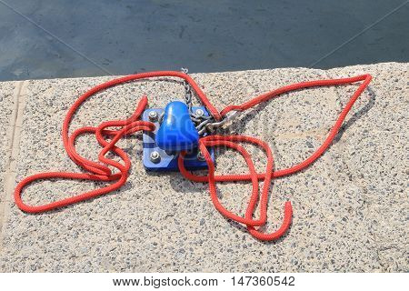 Blue Harbor Bollard With Red Rope On A Concrete Harbour Quayside