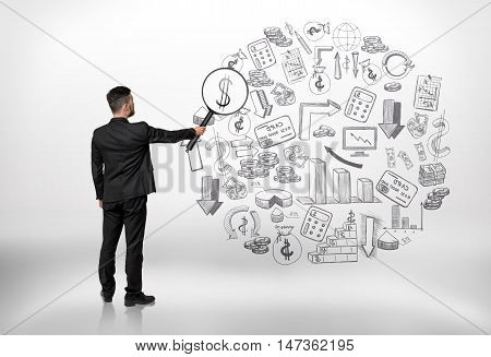 Back view of a businessman looking at business doodles through a magnifier and seeing dollar sign. Successful management. Investigation and research.