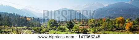 Vibrant autumn panorama background of Pirin, Bulgaria with colorful green, red and yellow trees and mountains peaks