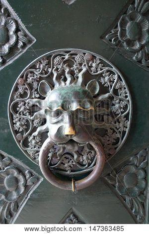 Old Door knoker. Door handle in the form of a lion's head. Detail of the shabby door.