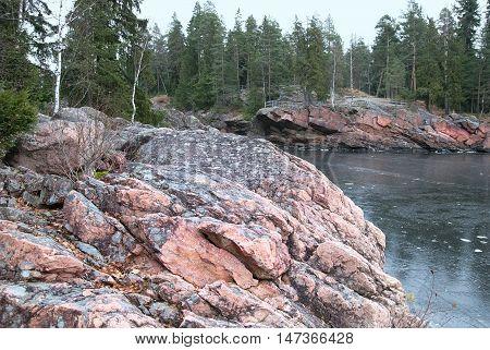 Imatra. Finland. Granite boulders on The Vuoksi River next to The Imatrankoski Rapids. On the background is The Kruununpuisto Park