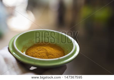 Turmeric powder in a green bowl. Closeup