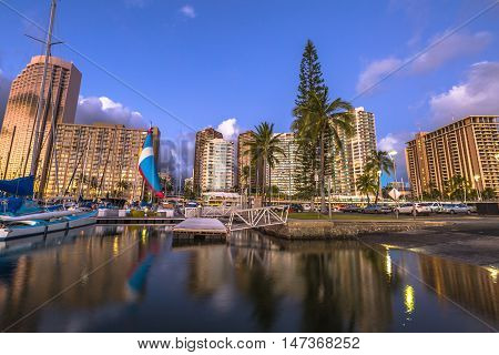 Boats and yachts docked at the Ala Wai Harbor the largest yacht harbor of Hawaii and Honolulu skyline at sunset. On background a luxurious hotel near Waikiki beach in Honolulu in Oahu Hawaii.