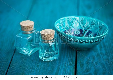 Blue ceramic bowl and two glass bottle on a wooden blue background