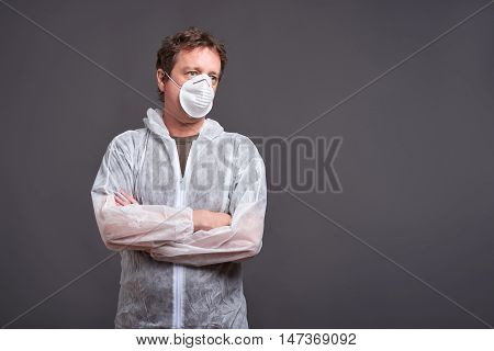 A middle aged man standing in a mask and in a clothes protector suit
