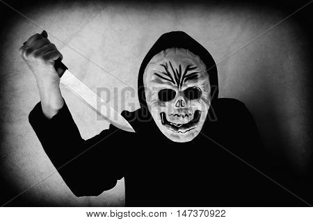 Woman in black with a human skull mask holding a knife. Low key. Computer added dirt, scratches, grain and vignette.