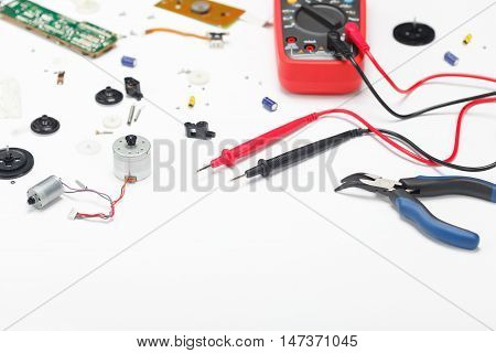Engineering mess background with multimeter electrical and mechanical parts. View above. Empty space
