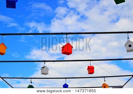 Bright colorful nesting boxes on blue sky.