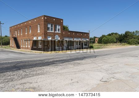 Old empty abandoned building with empty stores and shops at an intersection in a ghost town.