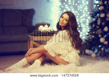 Cute girl or young woman sitting on floor in loft interior on christmas night. Fashion style portrait of trendy model