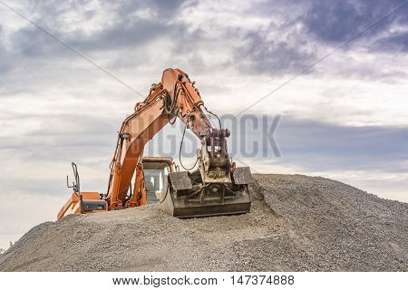 Excavator on top of a ballast pile - Frontal view of an orange excavator climbed on top of a ballast pile.