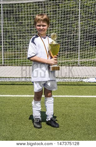Young Boy Keeps Proudly The Cup In Its Hand After The Game