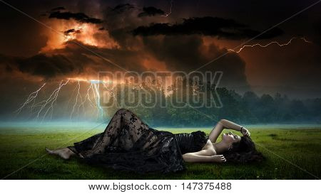 Composite image of a woman in black lace dress lying on grass with storm overhead