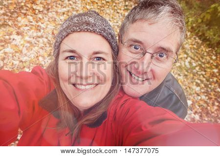 Middle aged couple taking a selfie in the fall, focus on the man
