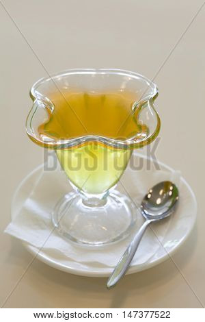 Jelly in glass plate, fruit gelatin dessert beige background. soft focus