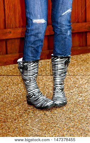 Woman in zebra print rain boots outside
