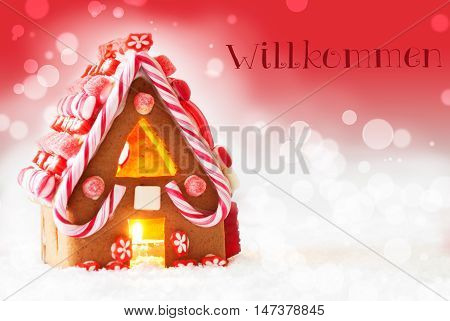 Gingerbread House In Snowy Scenery As Christmas Decoration. Candlelight For Romantic Atmosphere. Red Background With Bokeh Effect. German Text Willkommen Means Welcome