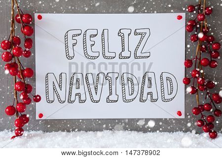 Label With Spanish Text Feliz Navidad Means Merry Christmas. Red Christmas Decoration On Snow. Urban And Modern Cement Wall As Background With Snowflakes.