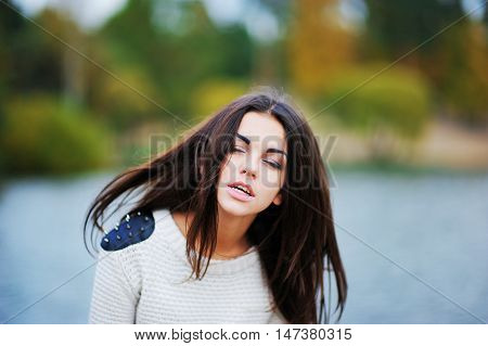 Young beautiful girl with flying in the wind hair and eyes veiled by the lake creating a soft background of the lake close-up.