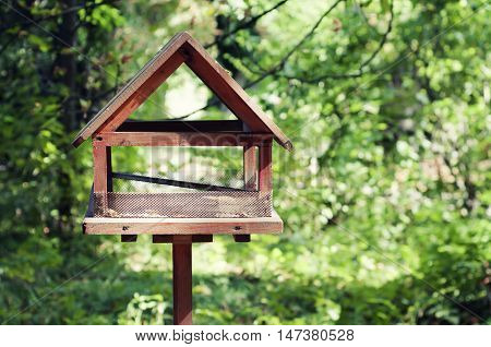 Bird house made of wood against bright green background