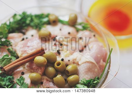 Raw chicken legs parsley cinnamon and spices in glass dish on white table close-up.