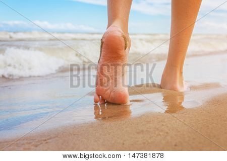 Closeup of a persons feet walking on the beach, focus on arch of foot and reflection in water
