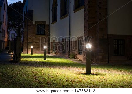 Outdoor lights (lanterns, bollards) in front of an old building illuminating a walkway in the garden at night