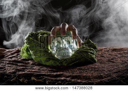 Spooky smoky scene of a hand grabbing a crystal skull