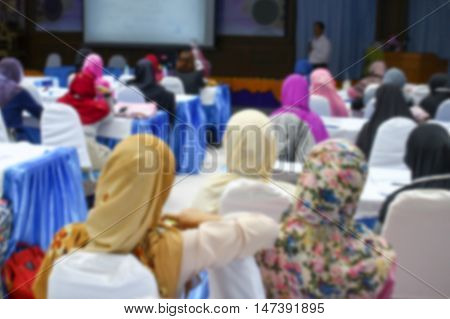 Blur blurred focus of university students. sitting in  lecture room  a teacher in front of the class with white projector slide screen : view from the back of the classroom: