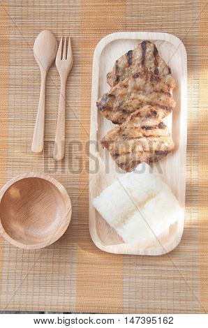 grilled pork eat with sticky rice on wood dish