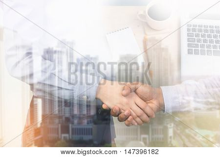Businessman handshake on the city and office desk background Double exposure of handshake with the city.