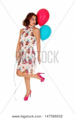 A beautiful young woman in a summer dress and heels holding two balloon's standing isolated for white background.
