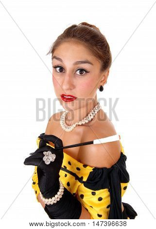A beautiful young woman in a yellow dress holding a long cigarette holder standing isolated for white background.