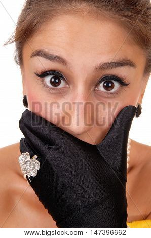 A closeup image if a woman's face with big eye's holding her mouth covered with black cloves isolated for white background.