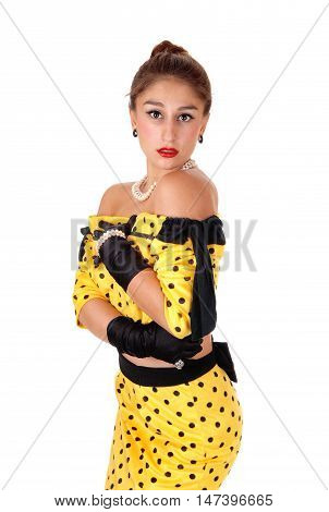 A beautiful young woman standing in a yellow dress and black cloves isolated for white background.