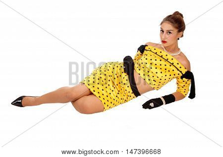 A beautiful young woman in a yellow dress and black cloves lying on the floor isolated for white background.