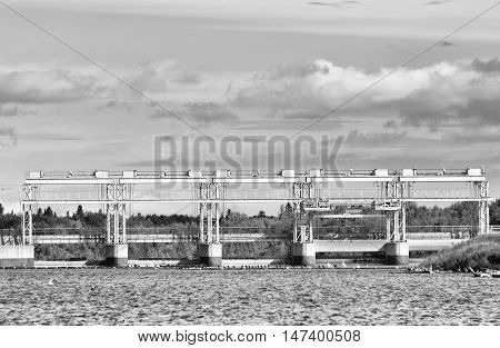 A close up of hydro electric station under cloudy sky in black and white