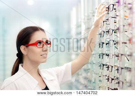 Happy Optician Choosing Between Eyeglasses Frames in Optics Shop