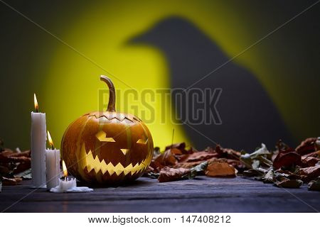Pumpkin for Halloween, lamp pumpkin, crow silhouette, antique wood, celebrating halloween, smiley on a pumpkin, paraffin candles, bright background, burning candles, autumn dry leaves