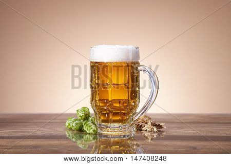 A glass of beer with a fresh, foamy beer in a glass mug, ears of wheat, ripe fruit hops, brewing ingredients, a wooden table