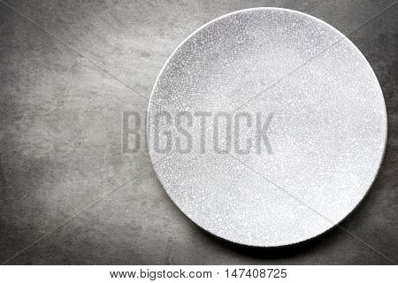 Empty plate over gray slate.  Top view.