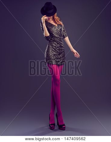 Fashion woman in Glamour Sequin black dress. Stylish Luxury Party lady. Redhead Sexy Model girl, Fashion Hat, Trendy Glamour fashion Heels, Pantyhose Long Legs. Fashion Pose. Unusual creative Outfit
