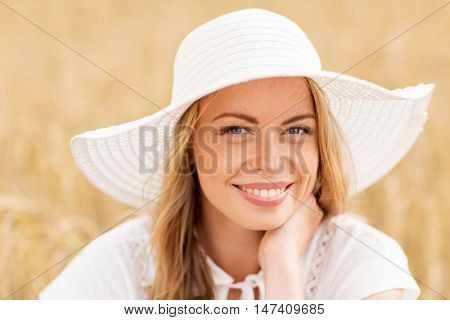 nature, summer holidays, vacation and people concept - close up of happy young woman in white dress and sun hat enjoying sun on cereal field