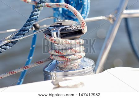 vacation, travel, cruise and yachting concept - close up of mooring rope on sailboat or sailing yacht deck and sea