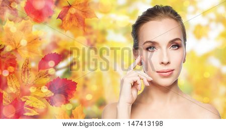 beauty, people and skin care concept - beautiful young woman showing her cheekbone over natural autumn leaves and lights background