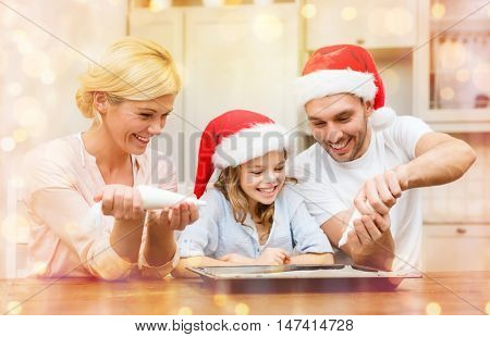 food, family, christmas, hapiness and people concept - smiling family in santa helper hats decorating cookies with glaze