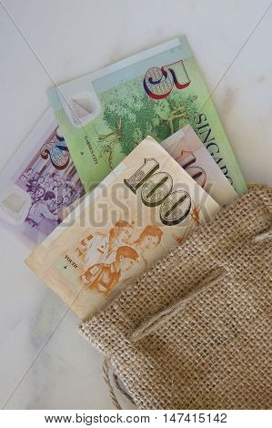 Some Singaporean notes in a hessian bag.